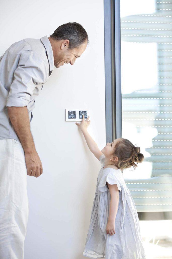 Op deze foto zie je een vader met zijn dochter een elektrisch raamdecoratie bedienen. Met elektrische bediening heb je geen losse koortjes meer.