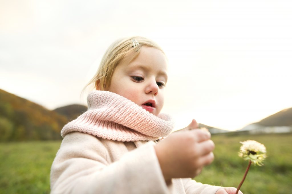 Meisje heeft bloem in haar handen. Stuifmeel dwarrelt rond.