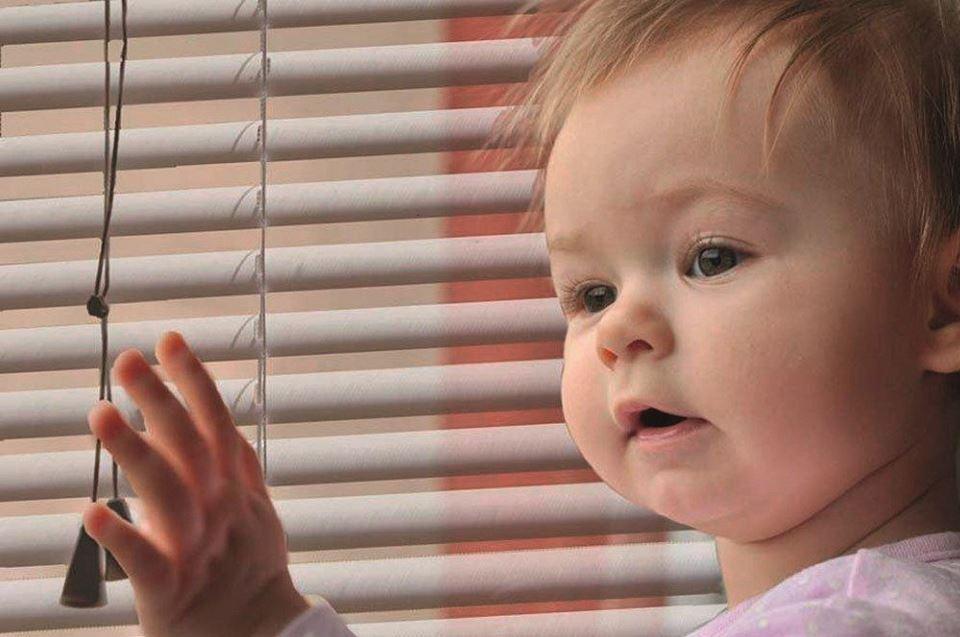Op deze afbeelding zie je een peuter dat aan een koord zit van een jaloezie. Zorg ervoor dat de koorden altijd buiten het bereik van kinderen zijn.